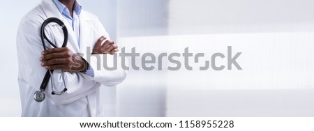 Panoramic View Of Male Doctor With Arms Crossed Holding Stethoscope #1158955228