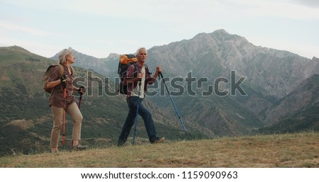 Active senior caucasian couple hiking in mountains with backpacks, enjoying their adventure 4k #1159090963