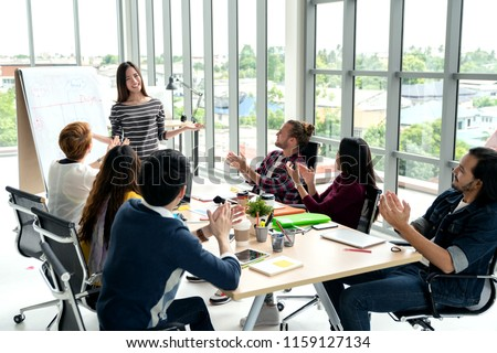 Young asian businesswoman explain idea to group of creative diverse team at modern office. Manager standing against rear view of multiethnic people. Audience applauding speaker after presentation. #1159127134