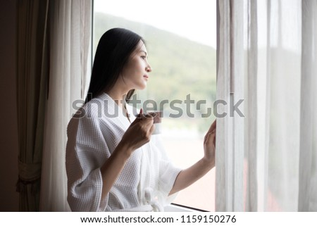 wake up :Woman in the morning holding a cup of tea or coffee and looking at the sunrise standing near the window in her home #1159150276