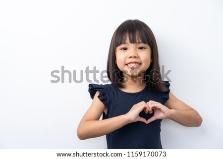 Portrait of cute kid with black hair making heart figure love sign with fingers isolated on white background