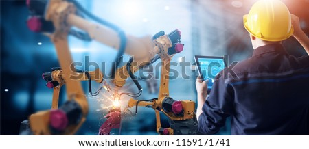 Engineer check and control welding robotics automatic arms machine in intelligent factory automotive industrial with monitoring system software. Digital manufacturing operation. Industry 4.0 Royalty-Free Stock Photo #1159171741