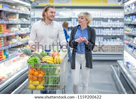 Shopping time. Positive man and woman shopping in grocery store, preparing to Christmas dinner. Couple enjoying in shopping, having fun together in shopping mall. Consumerism, love, lifestyle concept #1159200622