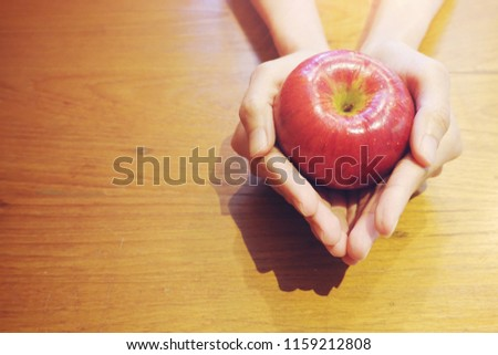 Hand holding red apple on wood table background, love yourself concept, healthy medical, you are what you eat concept,fruits, healthcare #1159212808