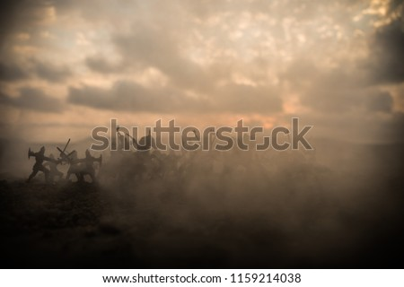 Medieval battle scene with cavalry and infantry. Silhouettes of figures as separate objects, fight between warriors on sunset foggy background. Selective focus Royalty-Free Stock Photo #1159214038