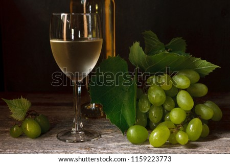 Green grapes with leaves, glass, bottle of white wine on vintage wooden background. Close-up, selective focus. Still life in vintage stile. Dark photo. #1159223773