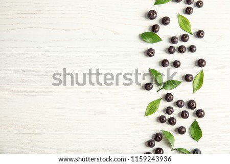 Flat lay composition with fresh acai berries and leaves on wooden background #1159243936
