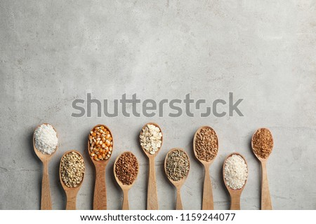 Flat lay composition with different types of grains and cereals on grey background Royalty-Free Stock Photo #1159244077