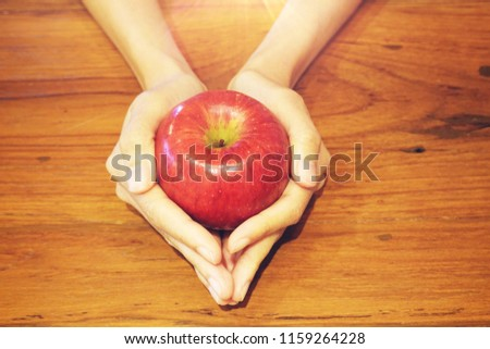 Hand holding red apple on wood table background, love yourself concept, healthy medical, you are what you eat concept,fruits, healthcare #1159264228