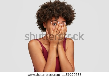 African American beautiful young female peeks though fingers, covers face with both hands, has frightened expression as notices something terrible or scarying, isolated over white background. #1159270753