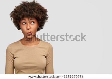 Young lovely female has dark skin, clueless and unaware expression, purses lips as being questionned, looks with puzzlement upwards, isolated over white background with copy space on right side #1159270756