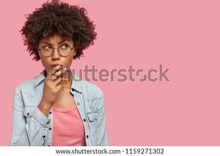 Pensive attractive curly African American female being deep in thoughts, raises eyebrows, curves lips, holds chin, wears fashionable clothes, stands against pink wall with copy space for your text #1159271302