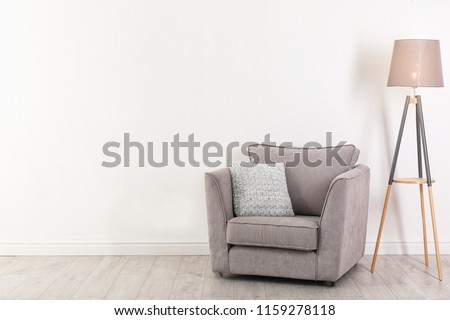 Comfortable armchair and lamp near wall with space for design. Stylish interior elements #1159278118