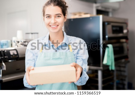 Waist up  portrait of smiling young  woman wearing apron holding box with takeaway food and looking at camera, copy space #1159366519