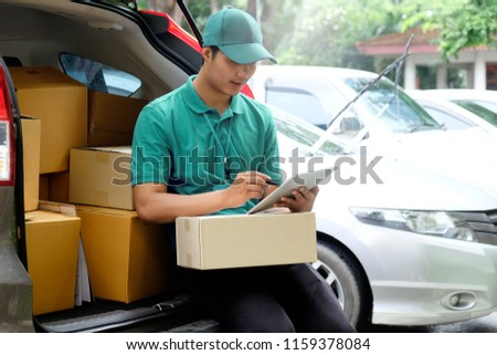 Portrait of a delivery Asian man standing in front of his van while checking a package #1159378084