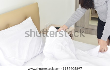 Make a bed, close up young woman holding bed sheet, working in the hotel concept #1159405897