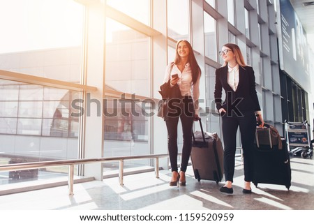 Two smiling business partners going on business trip carrying suitcases while walking through airport passageway #1159520959