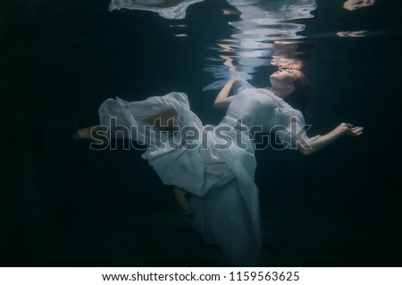 Beautiful woman in a white dress swims under the water. #1159563625