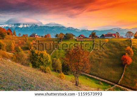 Beautiful autumn alpine landscape, famous alpine village with stunning colorful clouds and high snowy mountains in background near Bran, Magura village, Transylvania, Romania, Europe #1159573993