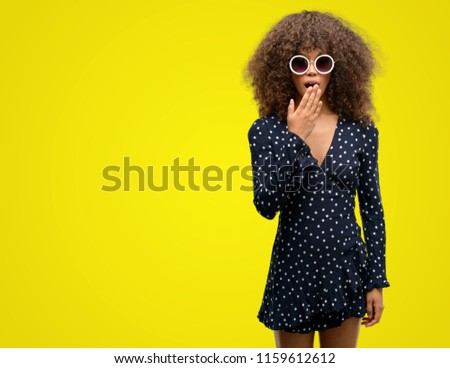 African american woman with sunglasses and summer dress cover mouth with hand shocked with shame for mistake, expression of fear, scared in silence, secret concept #1159612612