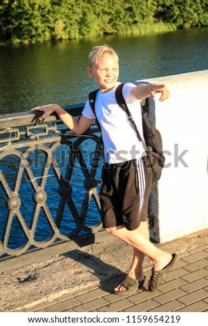 Tambov, Russia, August 2018: The boy stands on the embankment of the river, points a finger to the side #1159654219