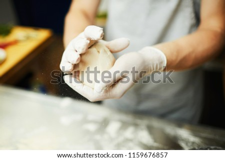 Gloved baker kneading piece of raw dough in his hands over table before rolling it for pizza #1159676857