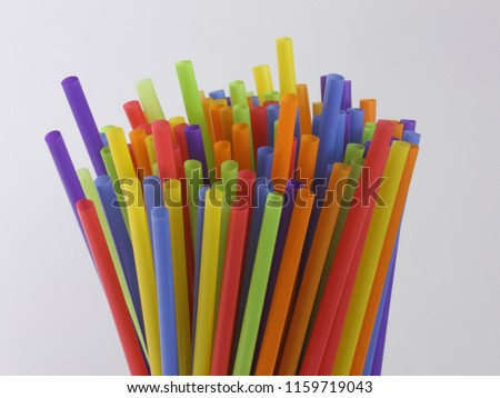 A bundle of colorful, single-use plastic straws are shown on display, stick up and isolated against a white background. #1159719043