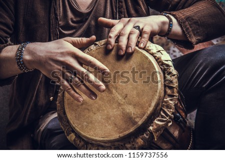 Ethnic percussion musical instrument jembe and male hands #1159737556