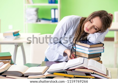 Young female student preparing for exams with many books  #1159769266