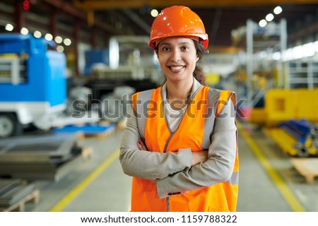 Waist up portrait of cheerful young woman wearing hardhat smiling happily looking at camera while posing confidently in production workshop, copy space #1159788322