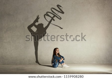 Baby girl dreaming about gymnast profession. Childhood and dream concept. Conceptual image with shadow of female gymnast on the studio wall #1159908280