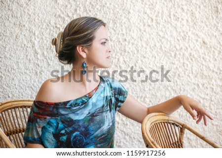 Portrait of elegant woman with long earrings on wall background #1159917256