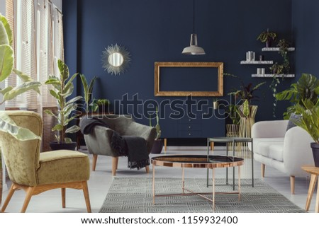 Copper table between armchairs and sofa in blue living room interior with mockup and mirror. Real photo #1159932400