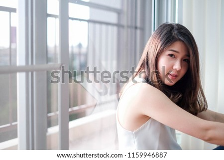 Young asian girl sitting next to the window, smiling to the camera. #1159946887