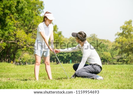 Golf trainer is training a new golf player #1159954693