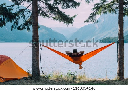 Back view of man silhouette relaxing on orange hammock between two trees pine enjoying the view at the lake in summer norwegian cloudy morning. #1160034148