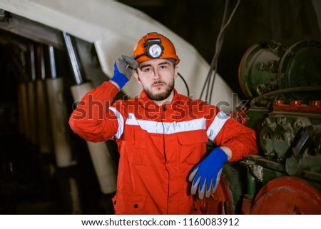 A young miner in a coal mine in the generals is busy working, repairing against the background of equipment. Portrait. the red form. #1160083912