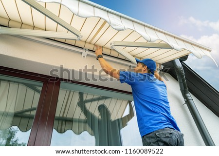 worker install an awning on the house wall over the terrace window #1160089522