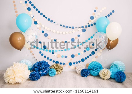 Photo zone with paper garlands, balloons, paper honeycombs, paper balls, pom poms and confetti.  Photo zone for birthday party and smash cake.  Blue, brown, gold, beige, turquoise colors.  Royalty-Free Stock Photo #1160114161