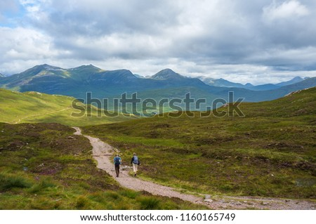 Hikers walking in Scottish mountains on West Highland Way under cloudy sky. #1160165749