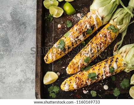 Grilled corn cobs with sauce, coriander, lime, paprika and cheese. Mexican food. Top view. Copy space #1160169733