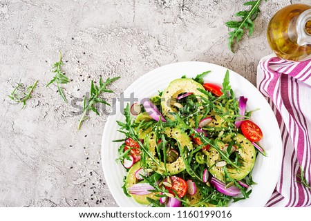 Diet menu. Healthy salad of fresh vegetables - tomatoes, avocado, arugula, radish and seeds on a bowl. Vegan food. Flat lay. Top view #1160199016