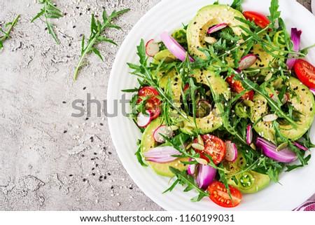 Diet menu. Healthy salad of fresh vegetables - tomatoes, avocado, arugula, radish and seeds on a bowl. Vegan food. Flat lay. Top view #1160199031