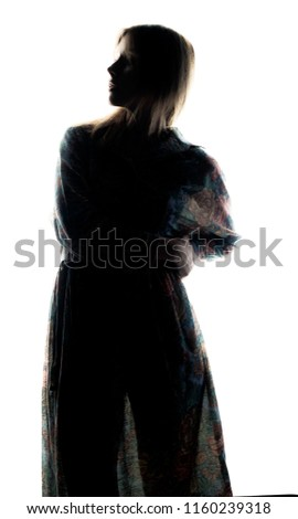 silhouette of a girl who stands in a pensive posture #1160239318