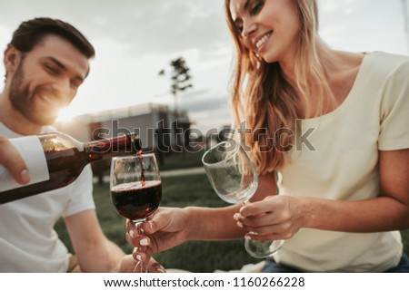 Satisfied male and positive young lady talking while having fun during lunch outside. They tasting appetizing red alcohol beverage #1160266228