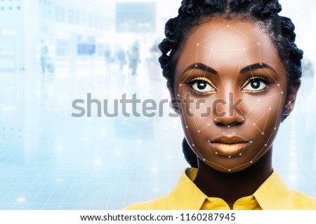 Close up portrait of attractive african woman with facial recognition technology. Grid with reference areas marked on face. Young girl against out of focus airport background.