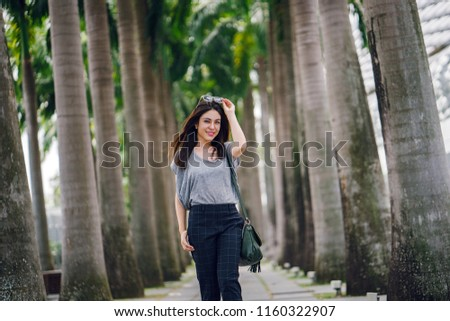 A young, cute and attractive Japanese Asian woman is smiling and posing for a photograph while on vacation in Singapore, Asia. She is posing with her sunglasses as the wind whips her hair. #1160322907