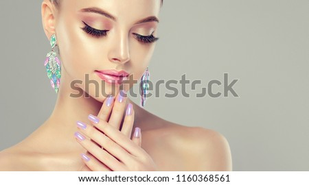 Beautiful model girl with pearl  color manicure on nails . Fashion makeup  and cosmetics . Big multicolored  turquoise shades  earrings jewelry . #1160368561