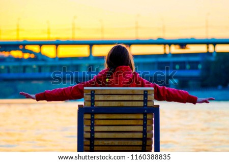 a woman sitting on a bench next to a river #1160388835