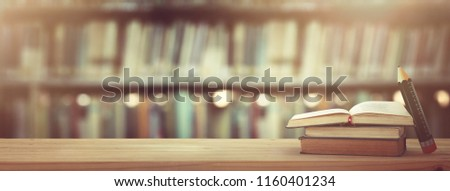 back to school concept. stack of books over wooden desk in front of library